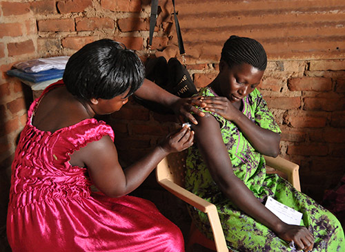 A community health worker with the Nawandala Village Health Team (VHT) gives the Sayana Press injection at her own home in Kiringa B Village, Uganda.