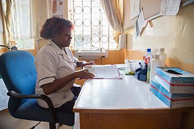 Kenyan nurse in a hospital at her desk