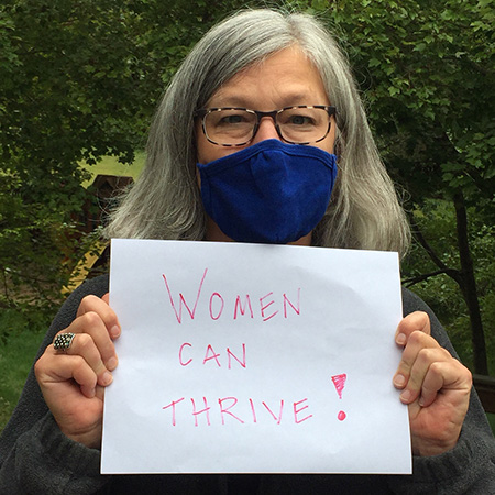 Anne Jorgensen, Technical Lead, Advocacy and Capacity Development, holds up a sign: Women can thrive!