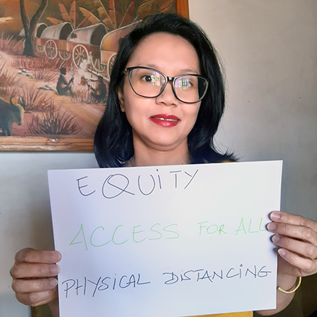 Elodie Randrianarijaona from HP+ Madagascar holds up a sign: Equity, Access for All, physical distancing
