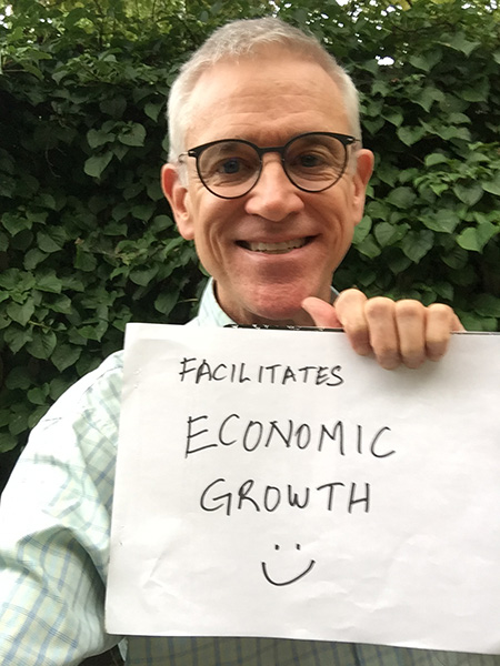 our author, Jay Gribble, holds up a sign: Facilitates economic growth - smiley face.