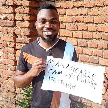 John Limited from HP+ Malawi holds up a sign: Manageable family- bright future