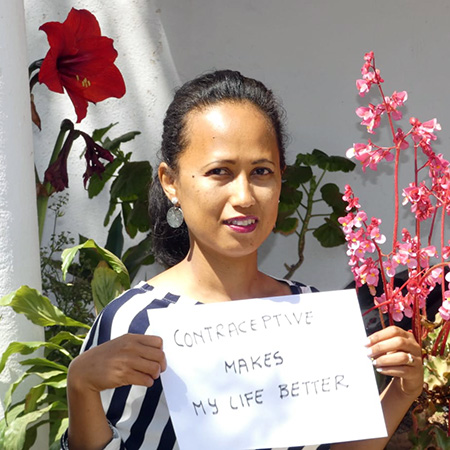 Norohaingo Andrianaivo of HP+ Madagascar, holds up a sign: Contraceptive makes my life better
