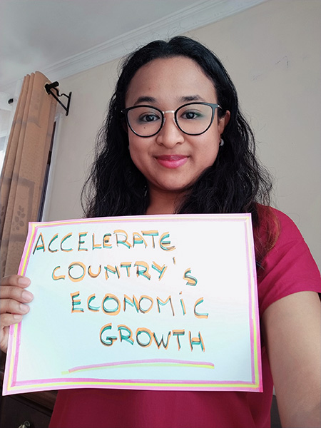 Stephanie Rakotoniaina of HP+ Madagascar holds up a sign: Accelerate country's economic growth
