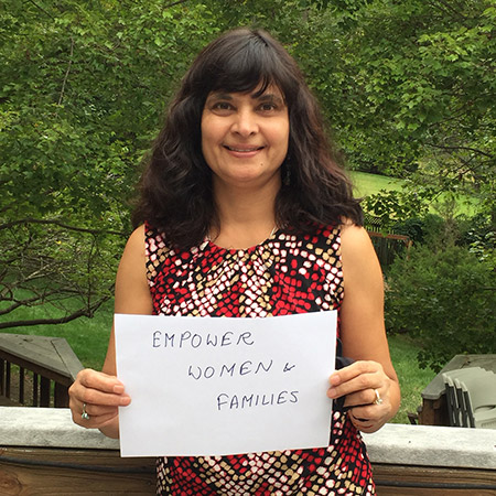 Suneeta Sharma, director of HP+, holds a sign that says: empower women and families