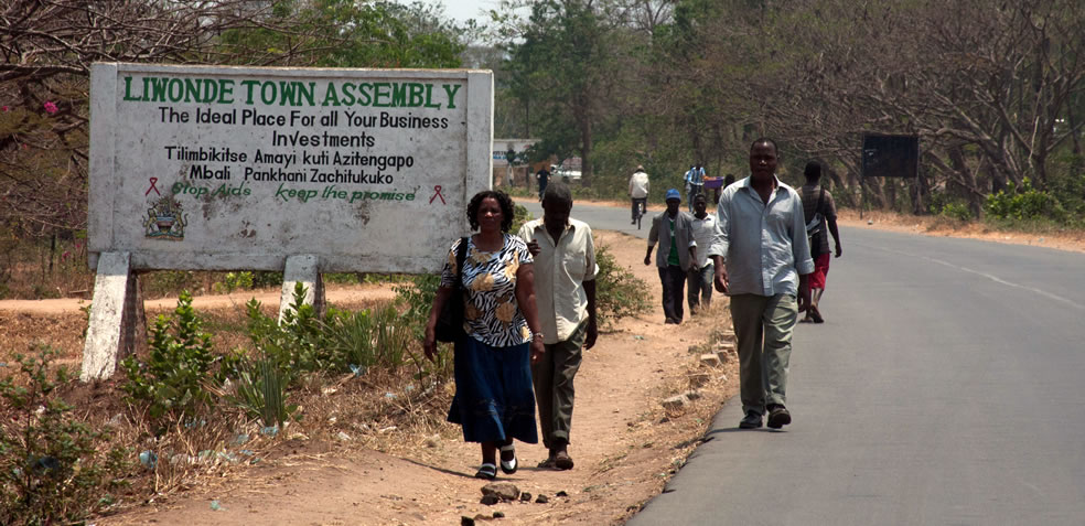 people walk along a street past a sign declaring the Liwonde Town Assembly is the ideal place for all your business investments, and advocatiing a end to aids